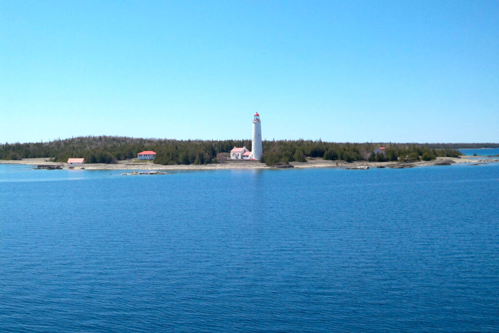 Lighthous on the edge of blue water - photo is taken from the waterside